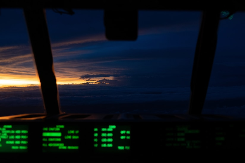 The sun shines through a sliver between dark clouds as seen from the cockpit of a military aircraft.