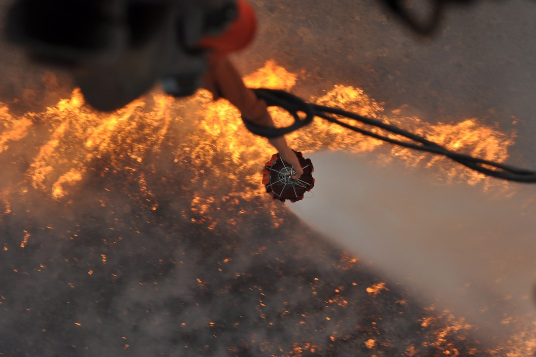 A helicopter empties  a water bucket over flames and smoke during a wildfire.