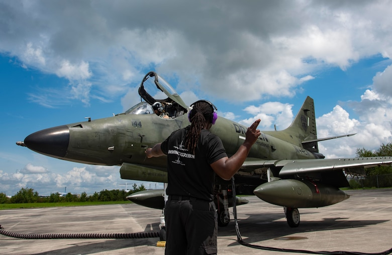 A crew chief ushers the pilot of an A-4K Skyhawk assigned to Draken International in preparation to taxi onto the runway at Kinston Regional Jetport, North Carolina, September 11, 2020. Draken works with the U.S. military to provide aerial threat simulation during exercises. (U.S. Air Force photo by Senior Airman Kylee Gardner)