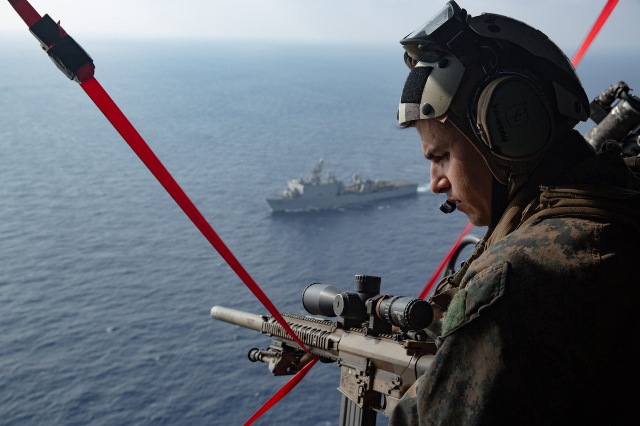A person with a gun looks out of a helicopter over the ocean.