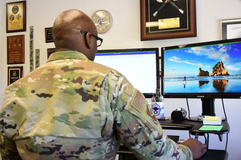 A photo of an Airman standing at his desk.