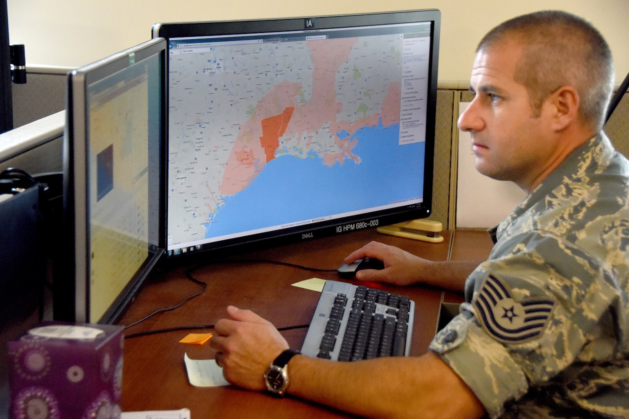 A man in a military uniform sits before two computer screens; one displays a map while the other displays related data.
