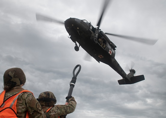 Two Soldiers under helicopter with rigging equipment.