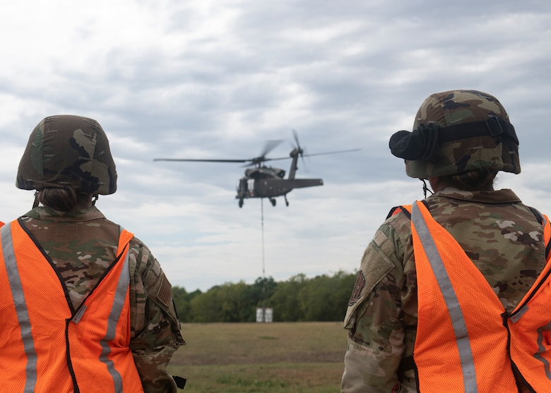 Two Soldiers watching a helicopter lift equipment.