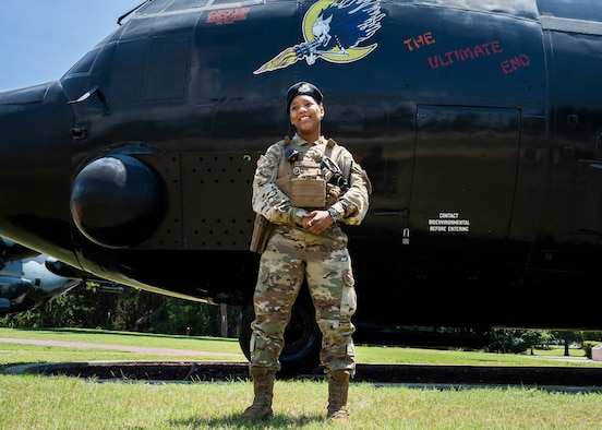 """Senior Airman Zatavia Funchess, 919th Special Operations Security Forces Squadron defender, poses for a photo in front of the """"Ultimate End"""" AC-130A Spectre at Hurlburt Field, Florida. Funchess has overcome numerous obstacles to reach her goal of becoming an Air Force Reservist. (Senior Airman Dylan Gentile)"""