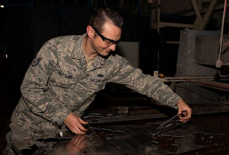 U.S. Air Force Staff Sgt. Derek Kettler, 48th Equipment Maintenance Squadron Fabrication Flight, removes an aircraft bracket from a sheet of aluminum at Royal Air Force Lakenheath, England, Sept. 15, 2020. The Fabrication Flight maintains the structural integrity of aircraft using specialized tools and equipment to repair damage and fabricate replacement parts, ensuring the 48th Fighter Wing remains a ready and capable force. (U.S. Air Force photo by Airman 1st Class Jessi Monte)