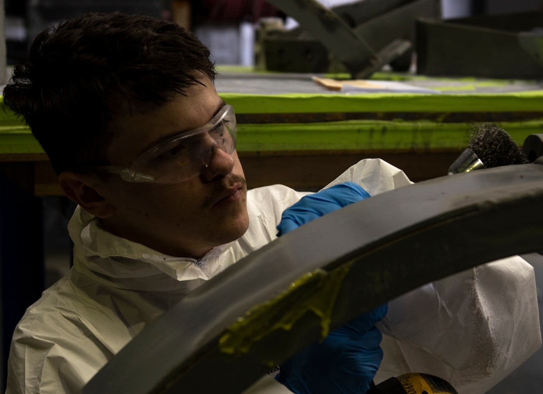 Senior Airman Tristan Casner, 48th Equipment Maintenance Squadron Fabrication Flight, uses a rotating wire brush to remove signs of corrosion from an aircraft component at Royal Air Force Lakenheath, England, Sept. 15, 2020. The Fabrication Flight maintains the structural integrity of aircraft using specialized tools and equipment to repair damage and fabricate replacement parts, ensuring the 48th Fighter Wing remains a ready and capable force. (U.S. Air Force photo by Airman 1st Class Jessi Monte)