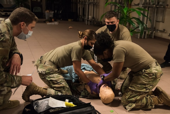4 medical personnel performing medical treatment on plastic dummy