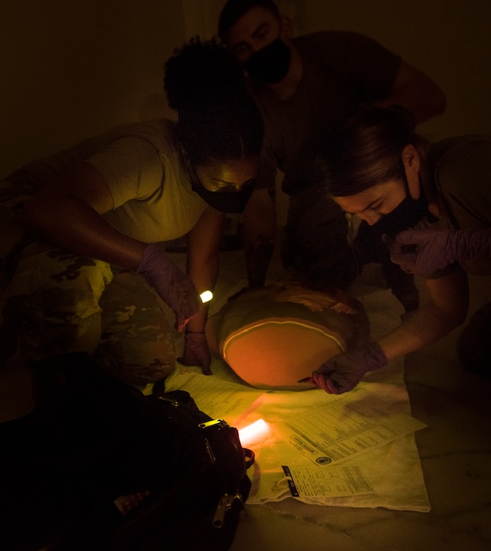 2 medical personnel using glow lights to write on paper