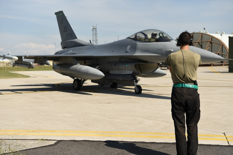 Senior Airman Cole McGriff, 555th Fighter Squadron crew chief, marshals a U.S. Air Force F-16 Fighting Falcon during exercise Point Blank 20-4 at Aviano Air Base, Italy, Sept. 10, 2020. Point Blank is a recurring, low-cost exercise initiative designed to increase the tactical proficiency of multiple forces. (U.S. Air Force photo by Staff Sgt. Heidi Goodsell)
