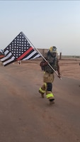 A firefighter assigned to the 409th Air Expeditionary Group carries a flag during a 9/11 remembrance march at Agadez Air Base 201, Niger, Sept. 11, 2020. Emergency services from around the base honored the victims of the tragic events that occurred 19 years ago. (Courtesy Photo)