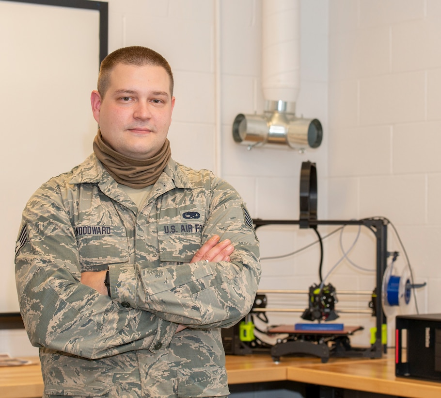 Staff Sgt. John Woodward, a metals technician with the 157th Maintenance Group, poses with a 3D printer, Pease Air National Guard Base, N.H, Sept. 3, 2020. Woodward used his background and education in metals technology to advance his shop's use of the 3D printer, allowing technicians to create prototypes, plastic tools and molds for crafting multifaceted equipment. (U.S. Air National Guard photo by Staff Sgt. Victoria Nelson)