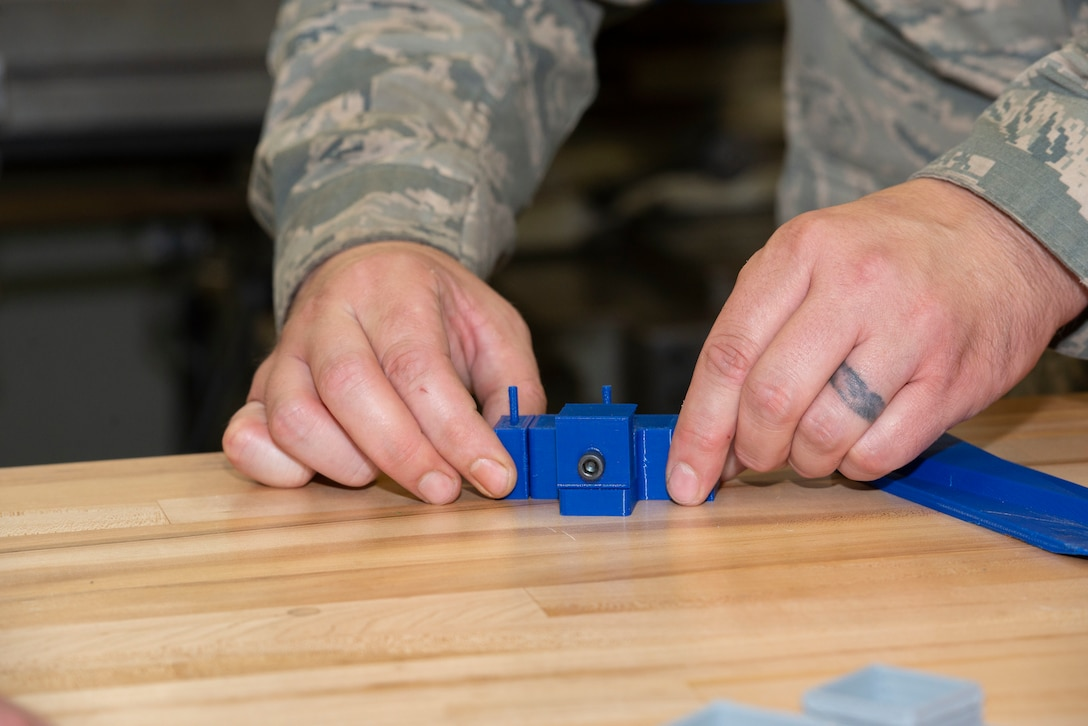 Staff Sgt. John Woodward, a metals technician with the 157th Maintenance Group, pieces together a 3D prototype designed to remove drain masts from the KC-46A without damaging the skin of the aircraft at Pease Air National Guard Base, N.H., Sept. 3, 2020. The printer allows technicians to create prototypes, plastic tools and molds for crafting multifaceted equipment. (U.S. Air National Guard photo by Staff Sgt. Victoria Nelson)