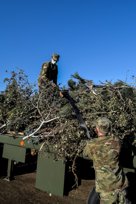 Utah Governor Gary Herbert stand with Soldiers at a debris waste collection site.