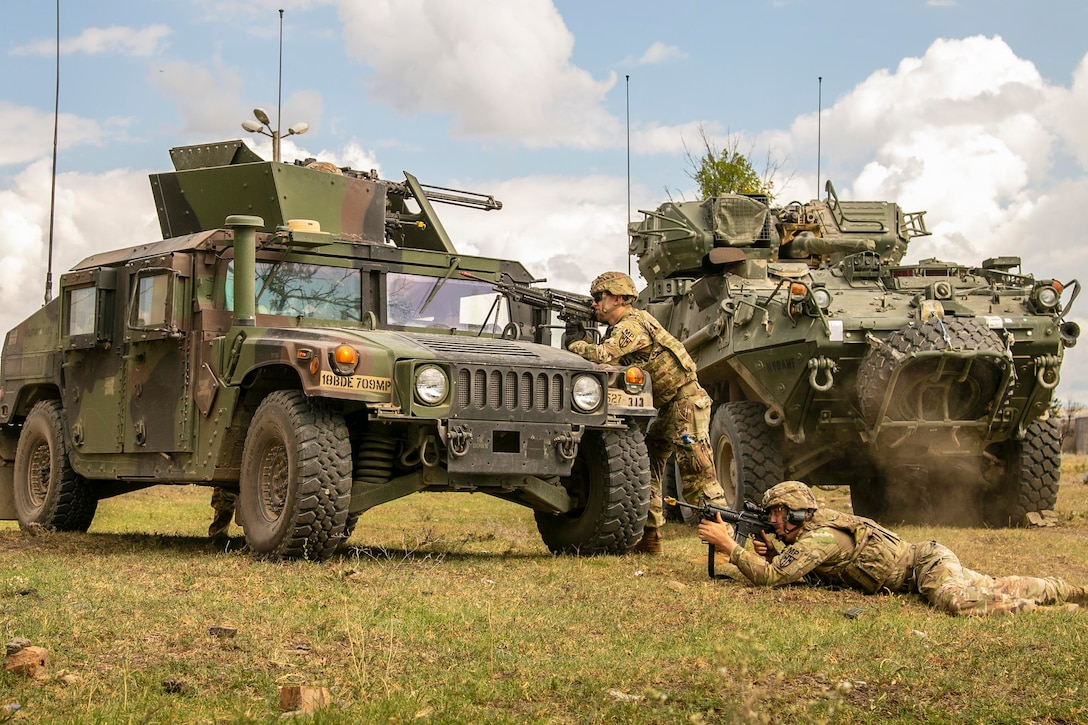 Two soldiers fire weapons from behind military vehicles.