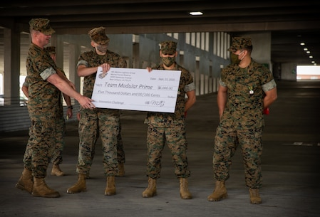 Brig. Gen. Karl Pierson, the commanding general of 4th Marine Logistics Group, present Marines with Special Purpose Marine Air-Ground Task Force - Southern Command with a cash prize during an award ceremony at Camp Lejeune, North Carolina, Sept. 15, 2020.