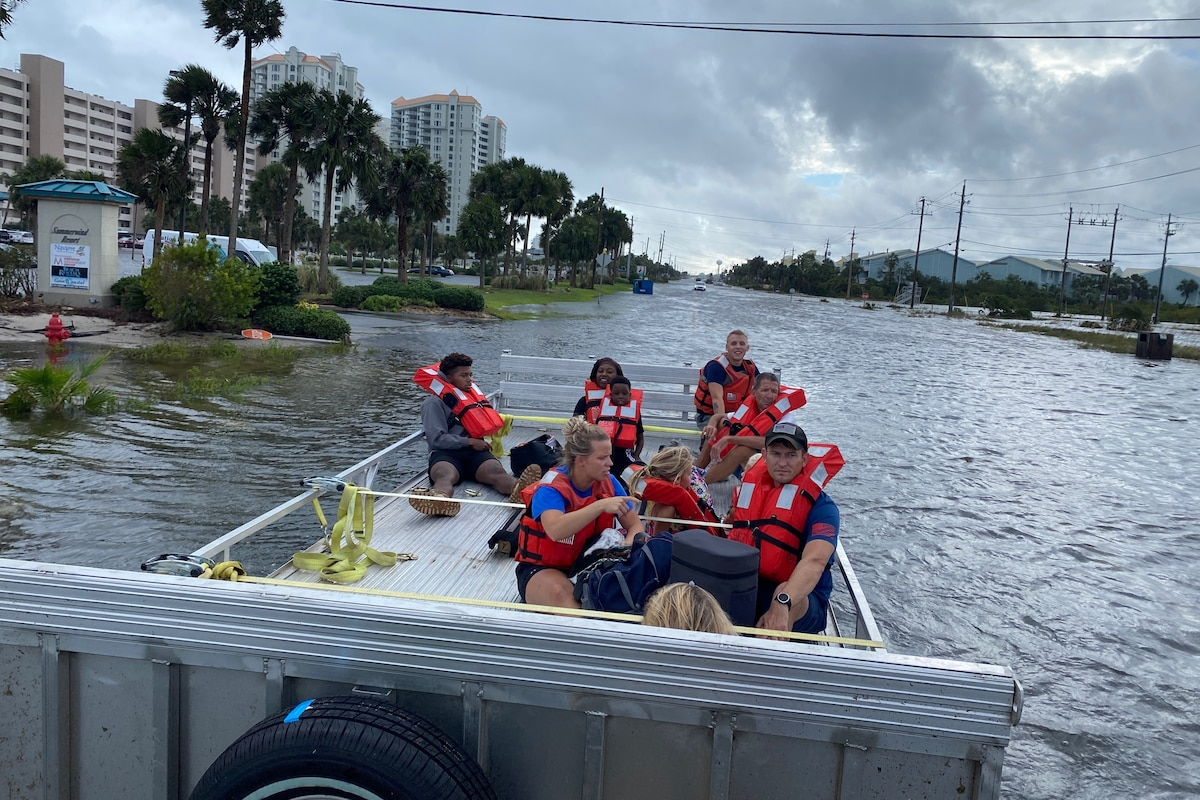 A boat carries a group of people and a dog through flooded streets.