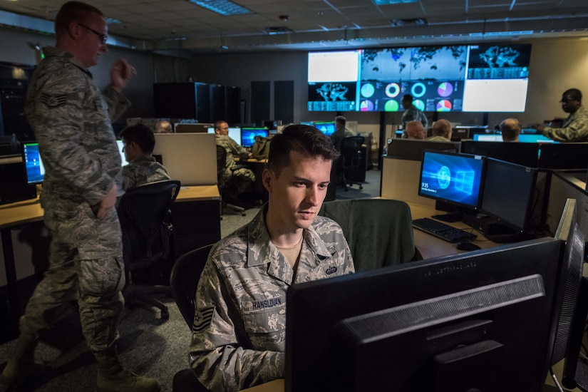 Airmen work on computers.