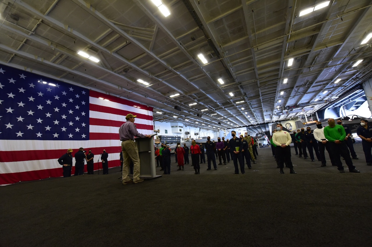 The defense secretary speaks to a group of sailors in a hangar bay on a ship.