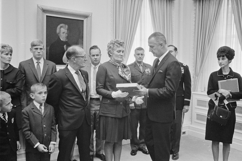A man hands a plaque to a woman surrounded by her family.