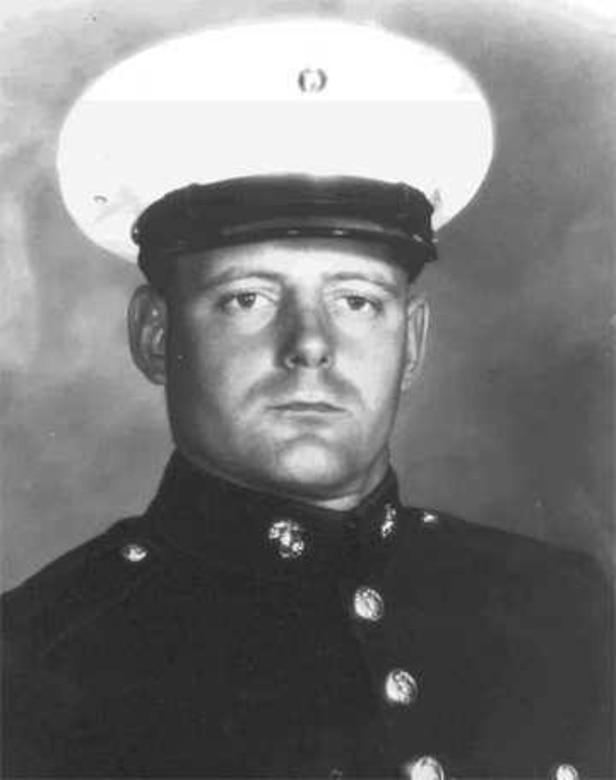 A man in uniform and cap looks forward.