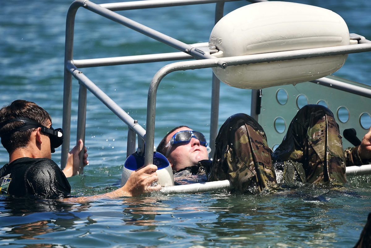 A service member moves another in underwater equipment during a water exercise.