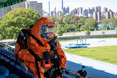 HAZMAT-suited technician searches outdoor stadium.