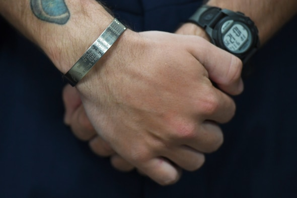 U.S. Air Force Airman Joshua Balmer, 737th Training Group basic military training graduate, wears a memorial bracelet during a presentation ceremony inside the Levitow Training Support Facility at Keesler Air Force Base, Mississippi, Sept. 11, 2020. Balmer, son of fallen Air Force Office of Special Investigations Special Agent Ryan Balmer, was presented mementos by the AFOSI Detachment 407 following his graduation from BMT. (U.S. Air Force photo by Kemberly Groue)