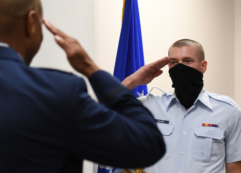 U.S. Air Force Airman Joshua Balmer, 737th Training Group basic military training graduate and son of fallen Air Force Office of Special Investigations Special Agent Ryan Balmer, salutes Special Agent Shannon Robinson, AFOSI Detachment 407 commander, during a presentation ceremony inside the Levitow Training Support Facility at Keesler Air Force Base, Mississippi, Sept. 11, 2020. Balmer was presented mementos by the detachment following his graduation from BMT. (U.S. Air Force photo by Kemberly Groue)
