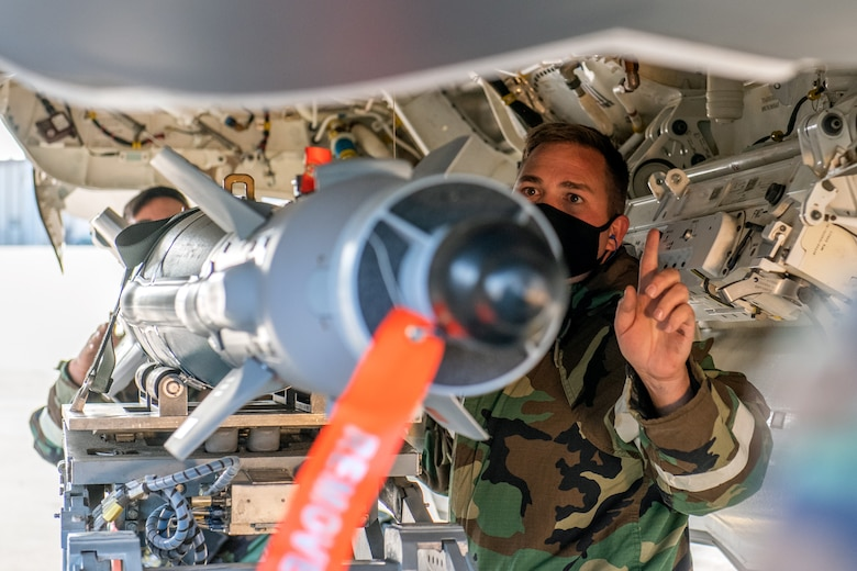 Tech. Sgt. Brian Hansen, a reservist in the 419th Aircraft Maintenance Squadron, guides a GBU-39 bomb into an F-35A Lightning II weapons bay
