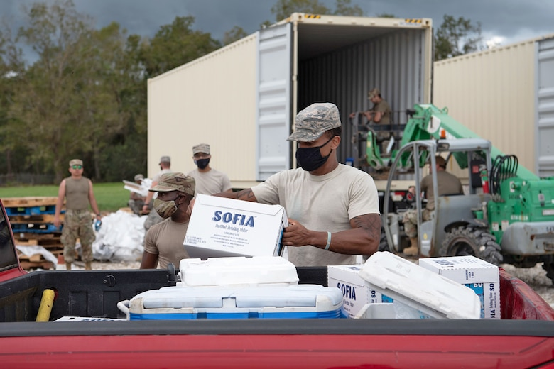 Airmen from the 159th Fighter Wing, Louisiana Air National Guard, load supplies in vehicles of residents affected by Hurricane Laura in Kinder, La., Aug 29, 2020.