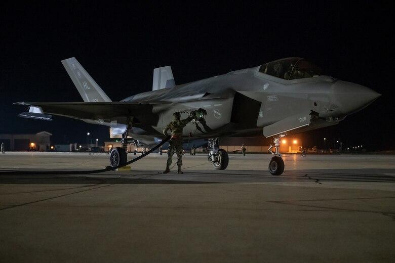 An Airman monitors an F-35A Lightning II during a hot pit refuel