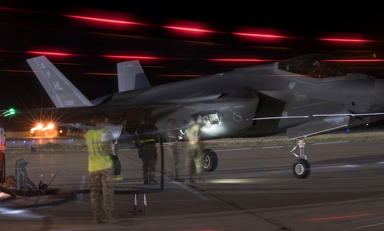 A slow shutter speed captures Airmen conducting a hot pit refueling of an F-35A Lightning II during night operations