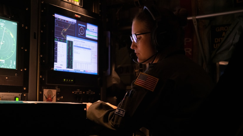 An airman sits in front of monitors.