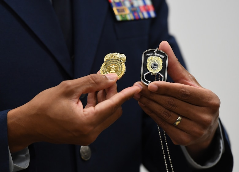U.S. Air Force Special Agent Shannon Robinson, Air Force Office of Special Investigations Detachment 407 commander, holds mementos during a presentation ceremony inside the Levitow Training Support Facility at Keesler Air Force Base, Mississippi, Sept. 11, 2020. Airman Joshua Balmer, 737th Training Group basic military training graduate and son of fallen OSI Special Agent Ryan Balmer, was presented mementos by the detachment following his graduation from BMT. (U.S. Air Force photo by Kemberly Groue)