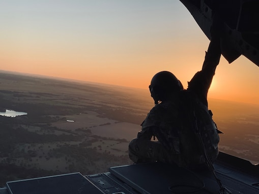 U.S. Army Staff Sgt. Brad Whitt, crew chief with Bravo Company, 2-104th General Support Aviation Battalion, 28th Expeditionary Combat Aviation Brigade, sits on a ramp and looks at the sunset out the back of a CH-47 Chinook helicopter as it flies over the 28th ECAB's mobilization station at Fort Hood, Texas.