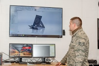 Staff Sgt. John Woodward, a metals technician with the 157th Maintenance Group, reviews a 3D printable mobile phone holder prototype at Pease Air National Guard Base, N.H., Sept. 3, 2020. The unit's 3D printer allows technicians to create prototypes, plastic tools and molds for crafting multifaceted equipment. (U.S. Air National Guard photo by Staff Sgt. Victoria Nelson)