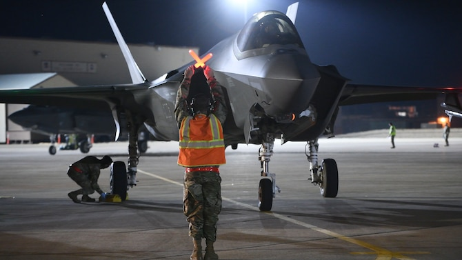 An Airman directs an F-35A Lightning II pilot to stop for a hot pit refuel with the aid of marshalling wands