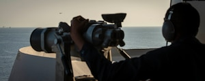 200918-N-ZR324-1014 STRAIT OF HORMUZ (Sept. 18, 2020) Seaman Antwon Brown monitors the horizon for surface and air contacts as the forward lookout aboard the aircraft carrier USS Nimitz (CVN 68) during a Strait of Hormuz transit, Sept. 18. The Nimitz Carrier Strike Group is deployed to the U.S. 5th Fleet area of operations in support of naval operations to ensure maritime stability and security in the Central Region, connecting the Mediterranean and the Pacific through the western Indian Ocean and three strategic choke points. With Nimitz as the flagship, deployed strike group assets include staffs, ships and aircraft of Carrier Strike Group 11, Destroyer Squadron 9, USS Princeton (CG 59) and Carrier Air Wing 17.  (U.S. Navy photo by Mass Communication Specialist 3rd Class Jose Madrigal)