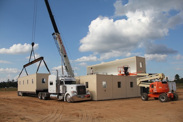 A Modular Anti-Ballistic, Blast and Forced Entry Resistant Shelter, or MABFERS, unit is lifted from a transport truck to be craned into position on the two-story structure. The U.S. Army Engineer Research and Development Center designed MABFERS to serve as personnel protection in high-threat locations abroad.