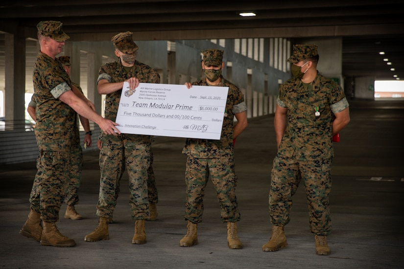 A Marine gives three Marines a large check.