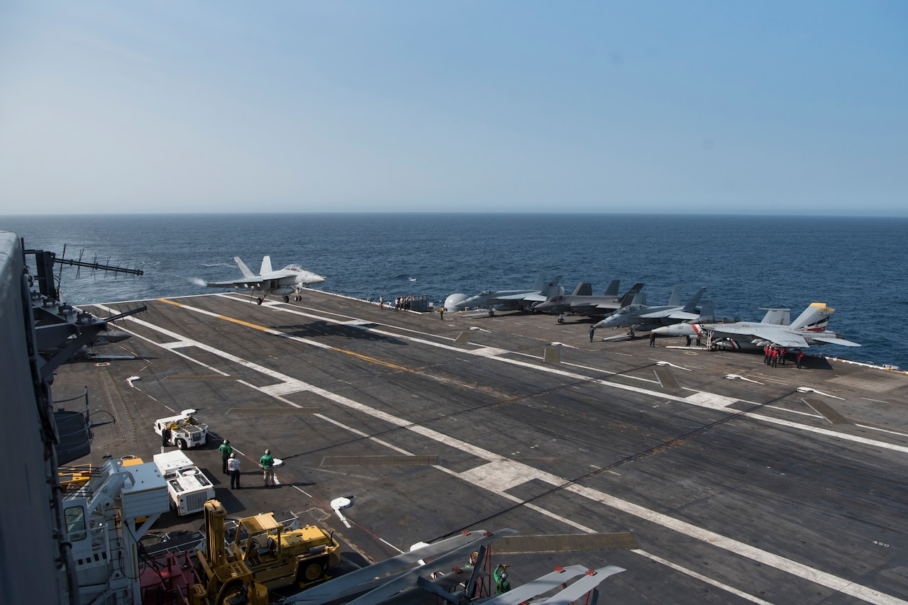 A fighter jet lands on the deck of an aircraft carrier as it sails on the ocean.