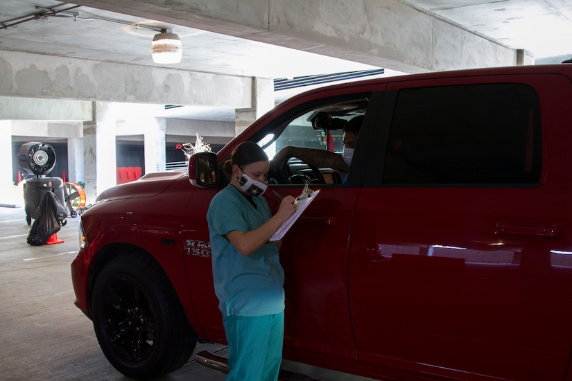 A medical soldier collects patient information at a COVID-19 drive-thru site.