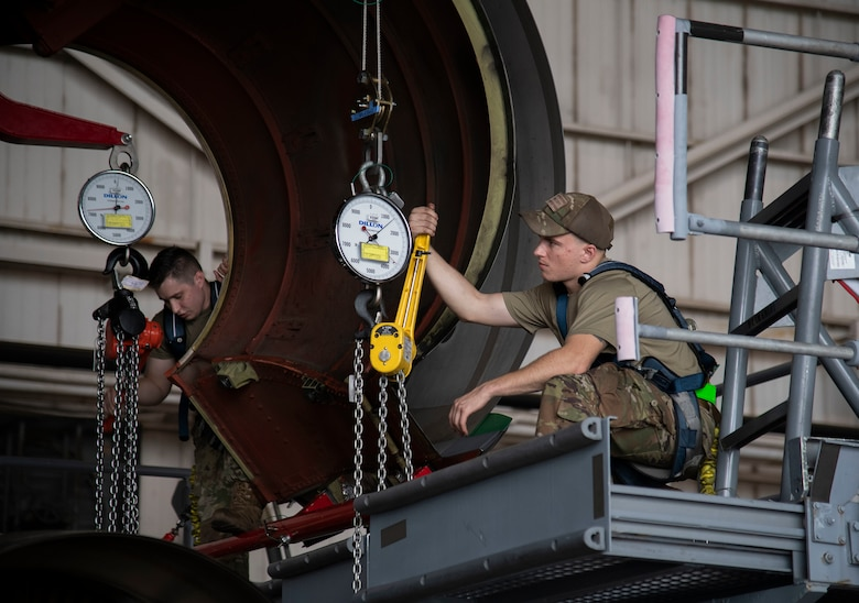 Airman 1st Class Tyler Jackson, 436th Aircraft Maintenance Squadron aerospace propulsion journeyman (right), and Senior Airman Derek Archer, 439th Aircraft Maintenance Squadron aerospace propulsion journeyman (left), utilize winches to lower the engine onto a cradle C-5M Super galaxy engine change September 9, 2020, at Dover Air Force Base, Delaware. Weighing between five to six tons and costing 15.5 million dollars, C-5M Super Galaxy engines are handled with precision and care. (U.S. Air Force photo by Airman 1st Class Jonathan Harding).