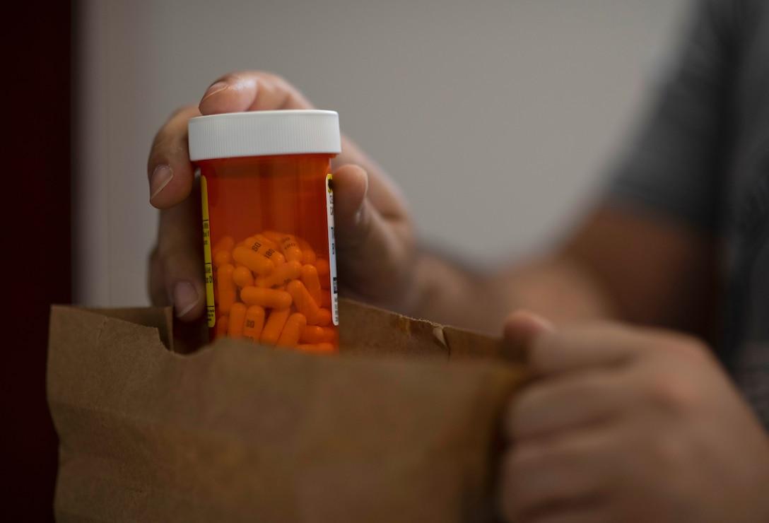 A service member places medications into a paper bag