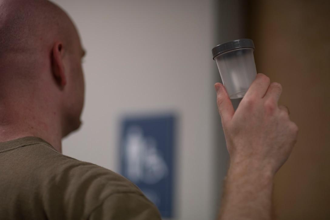 Service member holding up uranalysis sample