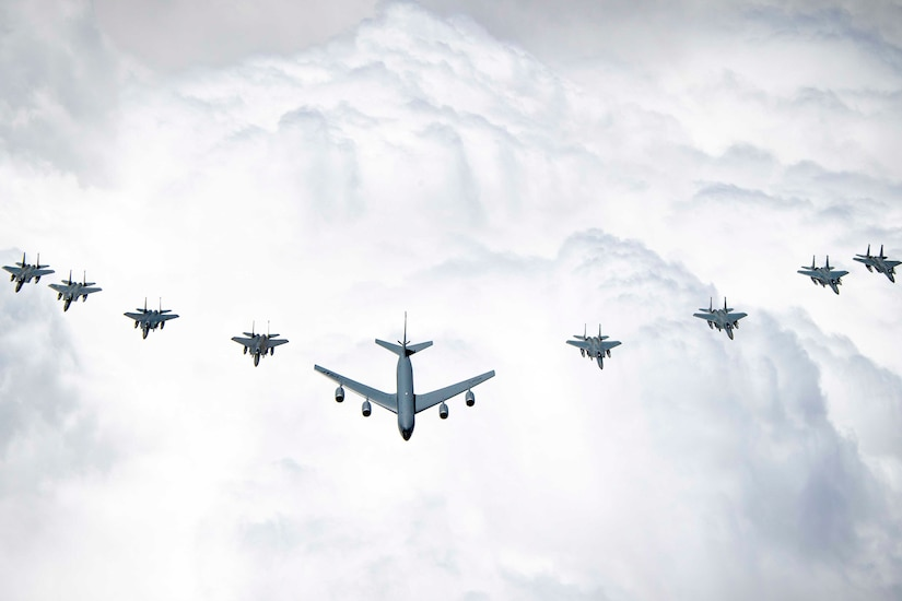 A large group of aircraft fly in formation.