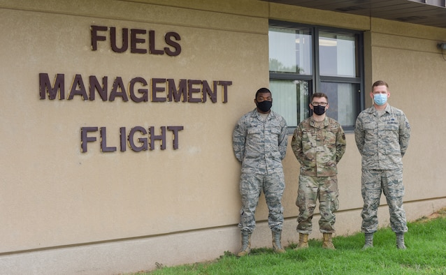 Three men stand in front of building