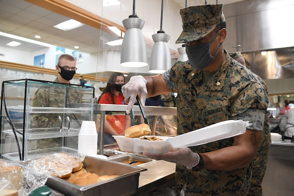 U.S. Marine Corps Maj. Adam Pinkney, Keesler Marine Detachment commanding officer, serves meals to Airmen inside the Azalea Dining Facility at Keesler Air Force Base, Mississippi, Sept. 18, 2020. As part of the Air Force's 73rd Birthday Celebration Week, Sept. 14-18, base leadership served meals to Airmen at the dining facilities. (U.S. Air Force photo by Kemberly Groue)
