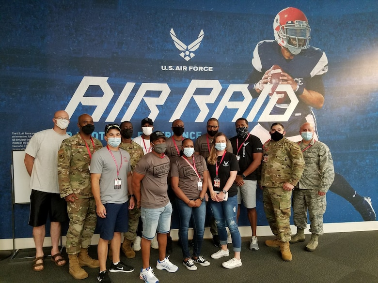 Total Force recruiters pose for a photo at the Chick-Fil-A College Football Hall of Fame, Aug. 28, 2020, in Atlanta Georgia. Air Force Recruiting Service recently signed a partnership with the HOF and the Air Force has a major exhibit called the Air Force Air Raid Quarterback Sim Experience.